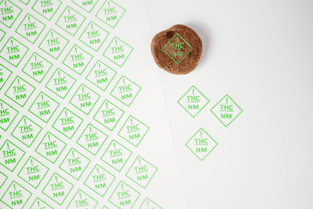 New Mexico THC symbol targets on cookie next to sheet